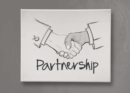 hand drawn handshake sign on canvas board as partnership business concept photo
