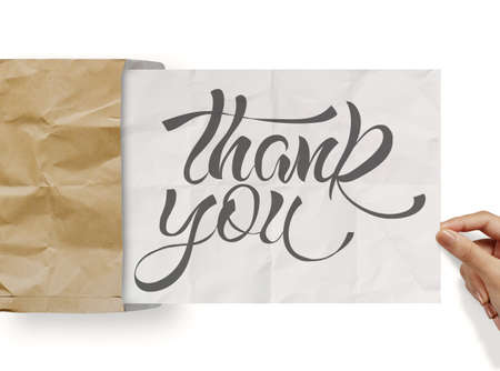 businessman hand show design word THANK YOU on crumpled paper as concept photo