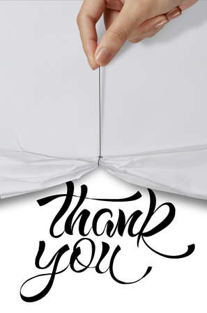 business hand pull rope open wrinkled paper show THANK YOU design text as concept photo