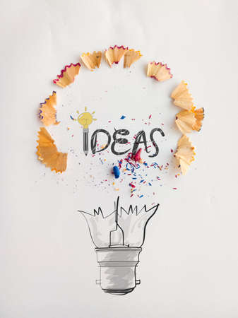 pape: hand drawn light bulb word design IDEA with pencil saw dust on paper as creative concept