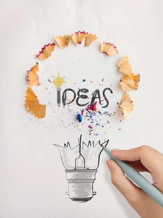 연필로 손으로 그린 전구 단어 디자인 아이디어는 창조적 인 개념으로 종이에 먼지를 보았다