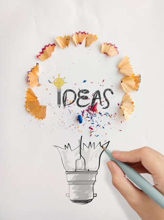 sharpen: hand drawn light bulb word design IDEA with pencil saw dust on paper as creative concept