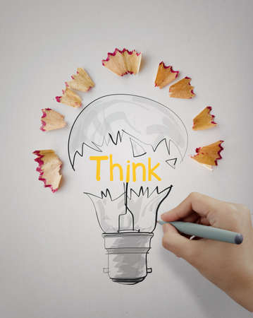 sharpen: hand drawn light bulb word design THINK with pencil saw dust on paper as creative concept