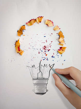 sharpen: hand drawn light bulb with pencil saw dust on paper as creative concept