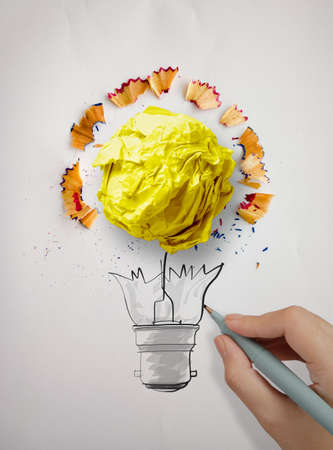 sharpen: hand drawing  light bulb and crumpled paper with pencil saw dust on paper as creative concept
