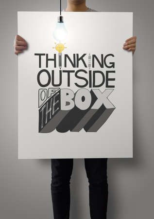 man showing poster of hand drawn  word THINKING OUTSIDE OF THE BOX with growing lightbulb as concept photo