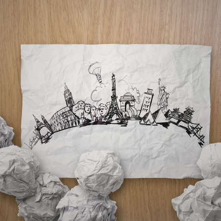 world travel: crumpled paper with hand drawn traveling around the world on wooden as concept