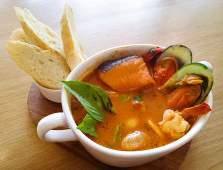 Delicious mediterranean seafood soup on wooden table photo