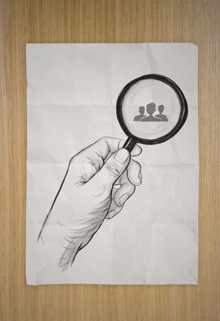 drawing of hand holding magnifier glass looking for employee on crumpled paper and wooden background as concept