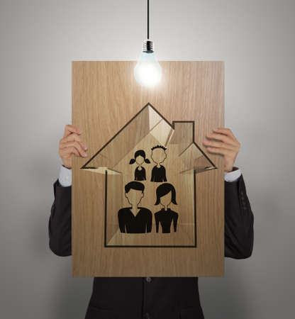 family relationships: businessman show hand draw family and house on wooden poster as insurance concept