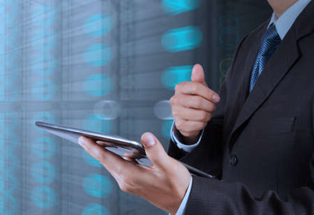 security: businessman hand using tablet computer and server room background