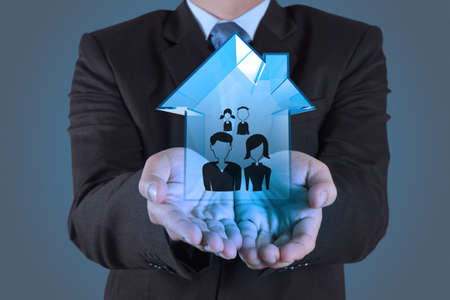 property management: businessman hand holding 3d house wtih family icon as insurance concept Stock Photo