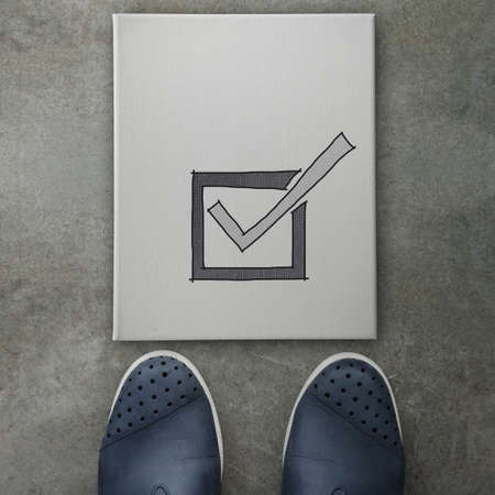 Hand drawn check mark  icon on canvas board on front of business man feet as concept  photo