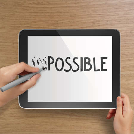 hand changing the word impossible to possible with stylus eraser on tablet computer as concept  photo