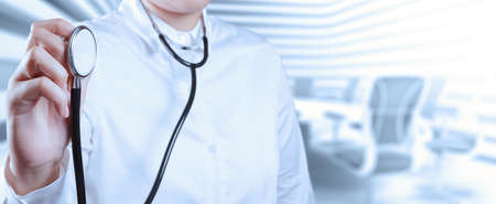 Doctor with a stethoscope in the hands and office background  photo