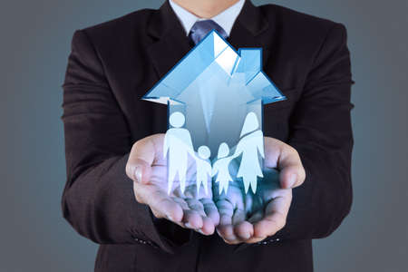 home protection: businessman hand holding 3d house with family icon as insurance concept