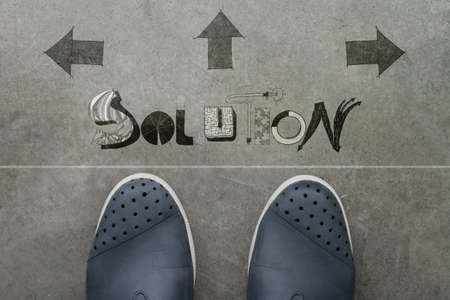 Hand drawn SOLUTION  design word on front of business man feet as concept  photo