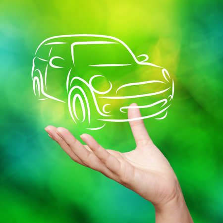 Hand with car against green nature sky background as concept photo