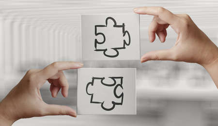synergism: Hand holding hand drawn  Partnership Puzzle icon on cavas board as concept  Stock Photo