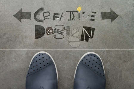 Hand drawn CREATIVE design word on front of business man feet as concept  photo