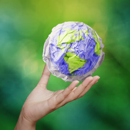 hand showing crumpled world paper symbol as concept on green background photo