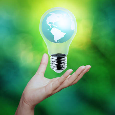hand holding planet earth in a lightbulb as energy concept photo