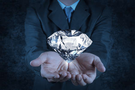 jewel hands: businessman hand holding 3d diamond as concept