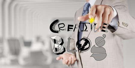 businessman hand draws creative blog word as concept photo