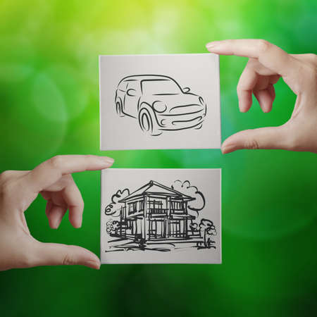 family budget: hand holding hand drawn house and car on canvas board on nature background as concept  Stock Photo
