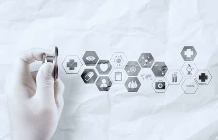 hand holding stethoscope shows medical icons on crumpled paper as concept photo