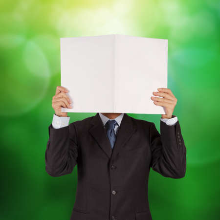 businessman with open book  over abstract light background as concept photo