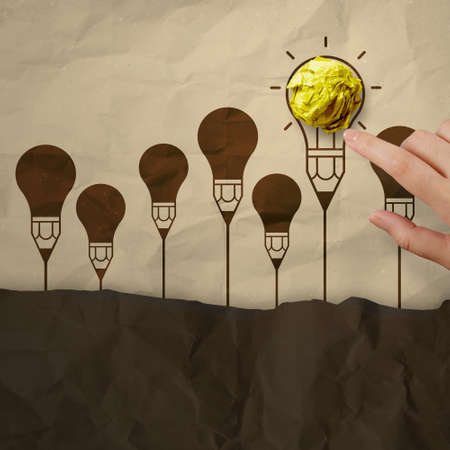 outside the box: hand pointing light bulb crumpled paper in pencil light bulb as creative concept