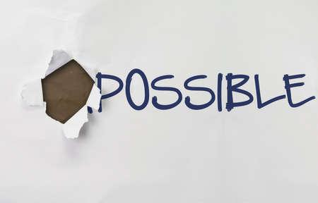 transformed: papel arrugado con la palabra imposible se transforma en posible en concepto