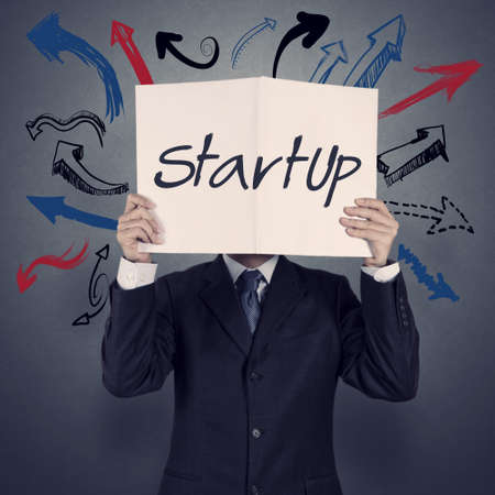 start up: businessman hand show book of startup business as concept