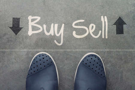 Hand drawn BUY or SELL design word on front of business man feet as concept