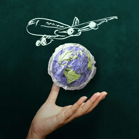 hand showing airplane with crumpled world paper symbol as concept on blackboard photo