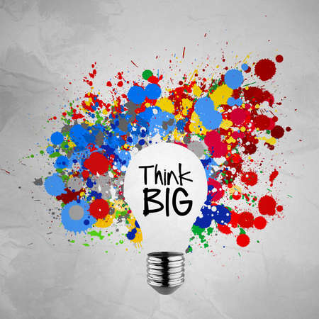 think big word with colorful splash colors lightbulb crumpled paper background as concept Imagens