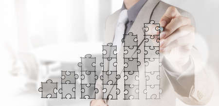businessman hand puzzle charts with new modern computer and business strategy as concept Foto de archivo