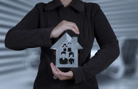 businessman hand holding 3d house with family icon as insurance concept photo