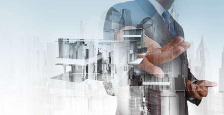 Dubbele belichting van zakenman kant presenteert huis model op moderne computer als ontwikkelingsconcept