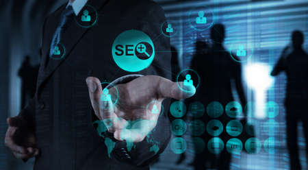 Double exposure of businessman hand showing search engine optimization SEO as concept