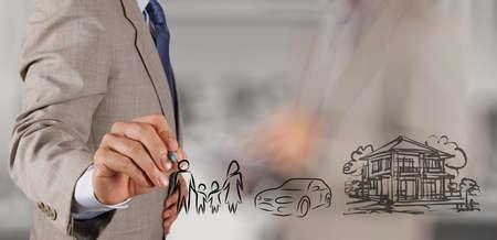 prosperidad: hombre de negocios mano muestran futura planificaci�n de la familia en el fondo de pantalla como concepto Foto de archivo