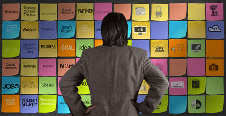 sticky hands: businessman looking at words icons of business strategy on sticky note as concept