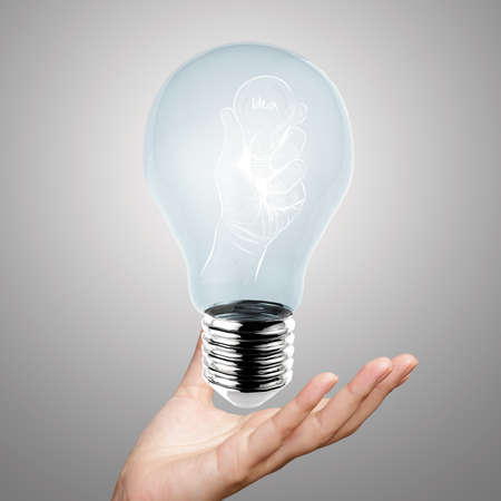 metal light bulb icon: hand reach light bulb of leadership concept