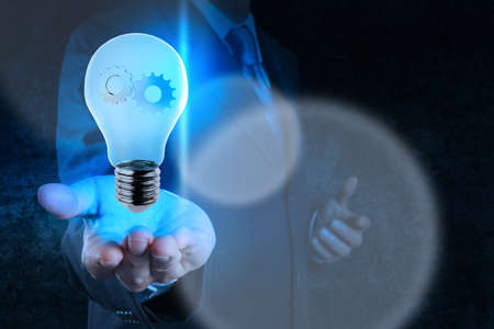 electrical engineering: businessman hand showing light bulb with gears as concept