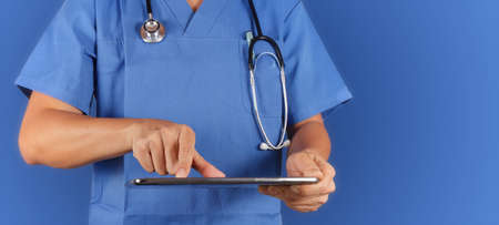 Doctor working with tablet computeron blue  background photo
