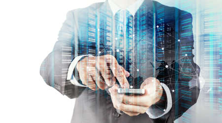 server room: Double exposure of Businessman hand using mobile phone and server room as concept Stock Photo