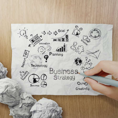 woden: hand drawing creative business strategy on crumpled paper with woden background as concept