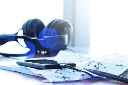 earphone: Closeup of smart phone with headphone on musical notes paper with shallow DOF evenly matched on wooden desk Stock Photo
