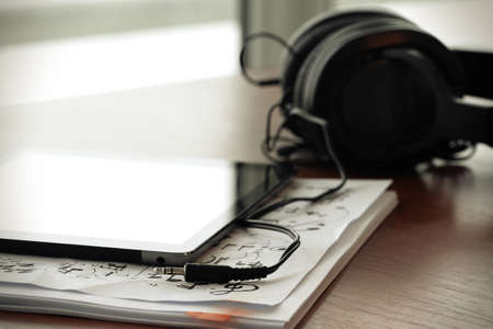 digital tablet with headphones on musical notes papers  with shallow DOF evenly matched and wooden desk photo